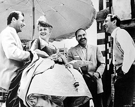 """Director DAVID MILLER, right, enjoys a laugh on the set of """"Diane,""""his 1956 historical drama, with, from left, actors LEX BARKER,LANA TURNER and PEDRO ARRMENDARIZ"""