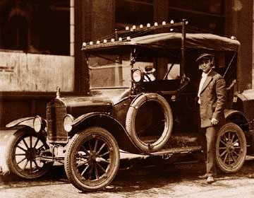 Patrolman and radio operator Walter Stick stands by one of the city's first radio-dispatched Police cars, a Ford Model T. Note the antennae on the roof.