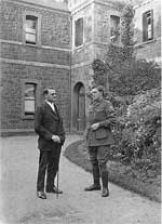 Image of two men, one in soldiers uniform, standing in front of bluestone building
