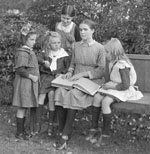 Photograph of a woman sitting on a park bench teaching four young girls Braille.