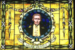 Framed and mounted stained glass window depicting the front head and shoulders profile of a man with the words