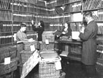 Photograph showing three women and a man at work in a library room lined with shelves of books. Several baskets of books are stacked in the centre of the room.