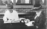 Image showing two women sitting at a table, copying text into Braille.